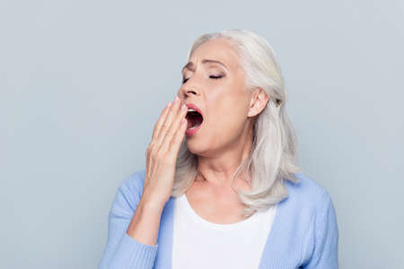 Portrait of tired, bored, attractive, aged, lazy woman in  closing her open mouth with palm, she wants to sleep, yawning over grey background