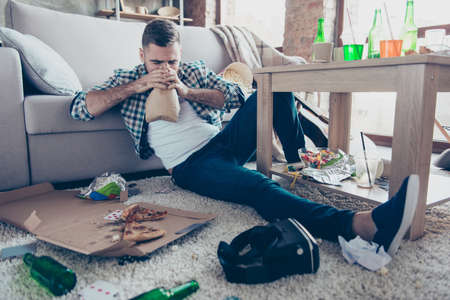 Drunk exhausted tired young man is suffering from nausea and panic attack, he is breathing in paper bag and sitting on the floor leaning on the sofa Stock Photo