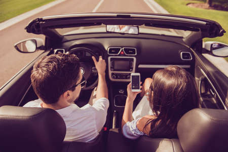 High angle shot of brunet driver husband, brunette lady wife show him screen of her pda, on their way to honeymoon. Married family, friendship, reach destination, escape, speed ride lifestyle Stock Photo