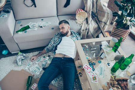 After party consequences. Top view above photo of drunk bearded wearing checkered shirt and jeans, he is sleeping on the floor and surrounded by money, popcorn, leftovers and mess Stock Photo