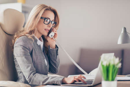 Portrait of successful, stylish, attractive, pretty, thoughtful businesswoman in glasses talking on phone with colleague, using laptop for work, having business phone conversation