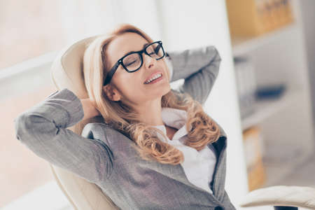 Close up portrait of joyful smiling happy cheerful charming beautiful wearing glasses and grey suit, she completed all tasks and now is having a rest