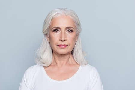 素敵な、魅力的な、老人、集中した、深刻な表情を持つ女性、灰色の背景の上に立っているの肖像 写真素材