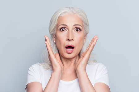 Pretty, nice, old, shocked, scared woman with wide open eyes and mouth in t-shirt holding palms near cheeks looking at camera over gray background