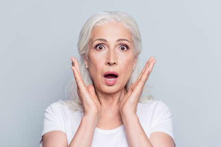 Jolie, belle, vieille, choquée, femme effrayée avec les yeux grands ouverts et la bouche en t-shirt tenant les paumes près des joues en regardant la caméra sur fond gris