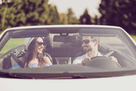 Married family, friendship, trip, relax, chill, escape, speed ride, valentine, honeymoon. Closeup of well dressed brunet driver in eyewear, femenine gorgeous cute brunette lady look at each other 스톡 콘텐츠