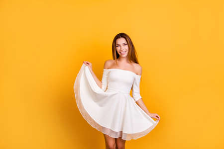 Ragazza sensuale e romantica con spalle nude, tenendo per il fondo della gonna, mostrando il suo vestito, guardando la telecamera in piedi su sfondo giallo