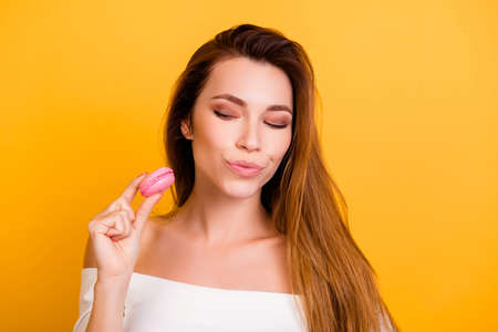 Delicious hesitate coquettish junk willpower sugar style stylish trend happiness cutting dream desire face idea concept. Closeup portrait of dreamy pretty lady holding cookies isolated on background Banco de Imagens