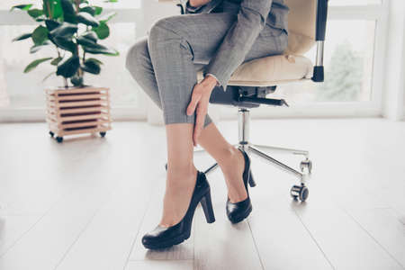 Concept of getting varicose because of wearing high heels. Cropped close up photo of womans legs wearing grey trousers and black modern shoes, hand is touching a leg