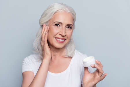 Perfect, pretty, woman using day, night cream, holding jar of cosmetic product looking at camera over gray background Фото со стока