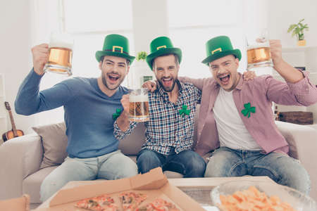 St Patricks day concept. Close up portrait of  cheerful, positive excited successful stylish lucky guys with bristle in green hats having glasses with lager in hands, looking at camera, yelling
