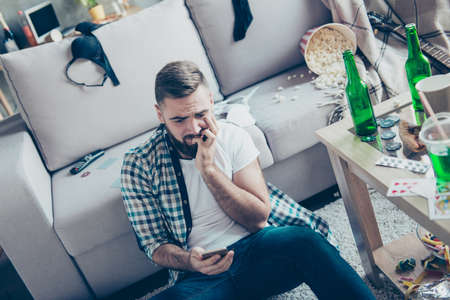 Sad upset troubled nervous bearded gut wearing casual checkered shirt and jeans is sitting on the carpet and watching shameful videos on his smartphone