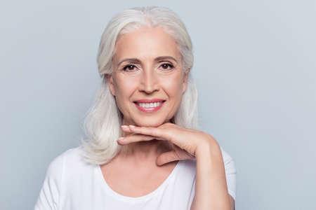 Charmante alte Frau , die Hand unter Kinn mit dem strahlenden Lächeln betrachtet Kamera über grauem Hintergrund hält