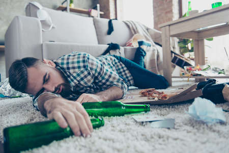 Sick drunk dreamy bearded guy clothed in checkered shirt and denim jeans is sleeping on the floor with an empty bottle in hand Archivio Fotografico