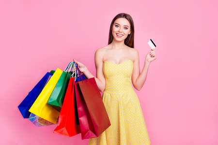 Portrait of delightful excited joyful cheerful attractive pretty in yellow dotted dress woman recommending to pay using credit card isolated on pink background Stock Photo