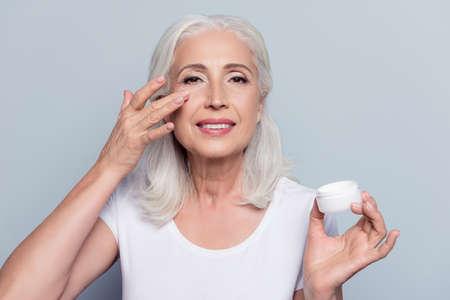 Mujer bonita, perfecta, aplicar crema para los ojos, sosteniendo el frasco de producto cosmético mirando a la cámara sobre fondo gris Foto de archivo
