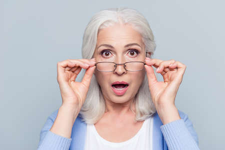 Close up portrait of stylish, aged, charming, surprised, shocked woman holding eyelets peek out glasses with wide open eyes and mouth over grey background 스톡 콘텐츠