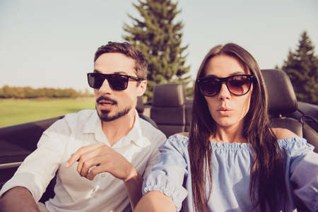 Oh no! Wtf! Close up of gorgeous brunette lady driver and her brunet guy panicking, both well dressed, in black trendy eyewear, park with green trees around, sunny day Stockfoto