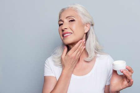 Rijpe volwassen senior vrouw met grijs haar zorgt voor haar gezicht en nek, ze smeert natuurlijke nachtcrème in met de hand voordat ze naar bed gaat, geïsoleerd op een grijze achtergrond