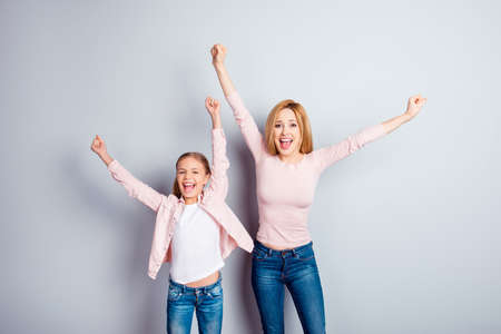 Yeah hooray people support victory triumph pleasure dream dreamy concept. Cheerful astonished amazed mum mama mommy cute lovely kid expressing rejoice bliss casual jeans isolated on gray background