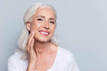 Bezaubernde, hübsche, alte Frau, die ihre perfekte weiche Gesichtshaut mit den Fingern, lächelnd an der Kamera über grauem Hintergrund, unter Verwendung des Tages, Nachtgesichtscreme, Cosmetologyverfahren berührt Standard-Bild