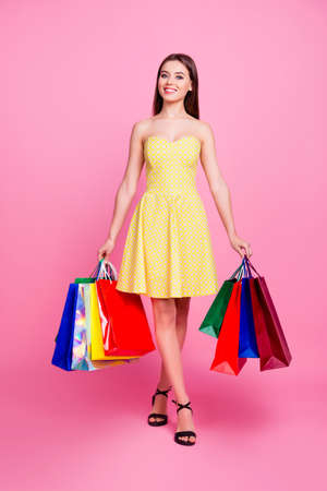 Vertical full-size full-length portrait of charming beautiful cute romantic perfect attractive pretty woman carrying many colorful bags with apparel isolated on background short dotted dress sandals Stock Photo