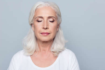 Portrait de femme mature concentrée confiante avec des rides sur le visage, les yeux fermés, avec du maquillage nu, isolé sur fond gris