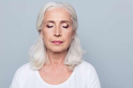 Schließen Sie herauf Porträt der überzeugten starken reifen Frau mit Falten auf Gesicht, mit geschlossenen Augen, wenn der Akt bildet, lokalisiert auf grauem Hintergrund