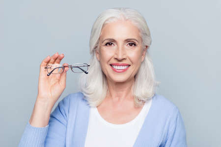 Old, charming, pretty woman showing glasses for sight, senior, people health care, standing over grey background Stock Photo