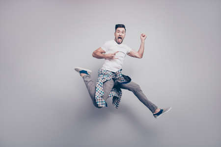 Happiness, freedom, motion and people concept. Crazy young bearded attractive handsome music lover jumping in air, gesturing rock and roll sign over grey background Stock Photo