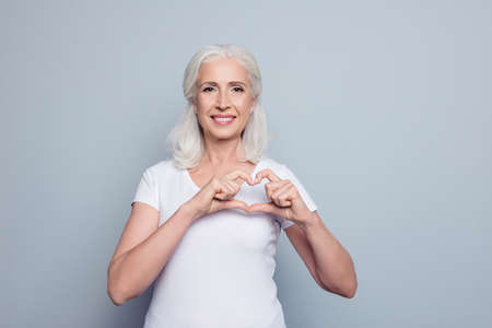Perfect, nice, aged, old, pretty woman, lover in t-shirt making, showing heart figure with fingers, looking at camera, celebrating womans day, standing over gray background Imagens