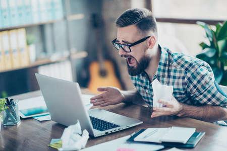 Boos gefrustreerd moe ongelukkig verrast kantoormedewerker draagt een geruit hemd zittend aan de tafel voor computerscherm, hij houdt verfrommeld documenten