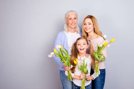People weekend joy leisure lifestyle motherhood parenthood maternity mama mommy concept. Portrait of adorable sweet gentle lovely beautiful three women standing together isolated on gray background Foto de archivo