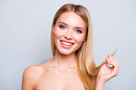 I dont need to cut the ends! Close up portrait of happy charming attractive gorgeous glad woman with toothy smile, showing healthy hair ends, isolated on grey background Stock Photo
