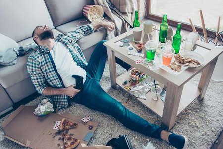 술에 취해 아픈 피곤 피곤 입고 체크 무늬 셔츠와 데님 청바지 수염 남자는 글로벌 홈 파티와 축하 후 엉망으로 남은 조이스틱을 들고 바닥에 앉아있다