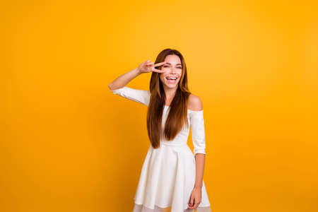 Leisure lifestyle people person celebrate flirt coquettish concept. Beautiful pretty cheerful gorgeous brunette showing making v-sign near eyes wearing elegant apparel isolated on yellow background