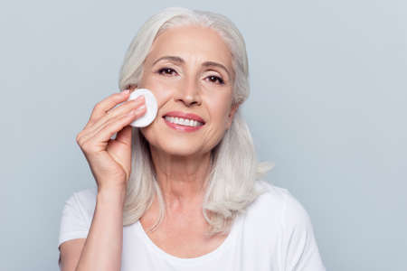 Excited cheerful confident lovely beautiful mature woman is using a cotton pad with micellar water  for removing make up from face, isolated on grey background, copy-space Stock Photo