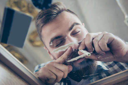 Close up portrait of happy excited feeling good bearded guy with stylish modern hair, he is sniffing cocaine through rolled banknote Stockfoto