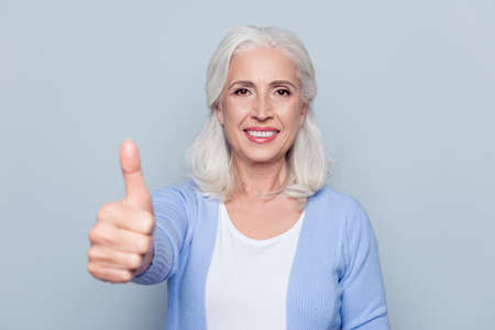 Close up portrait of happy joyful confident satisfied with shiny beaming smile mature woman grandmother granny grandma with gray hair, she is showing thumb-up, isolated on gray background