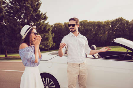 Well dressed rich husband present his wife a new vehicle outdoors. Success, happiness, sale, promotion, buyer, ownership, property, purchase, rent, sell cars concept