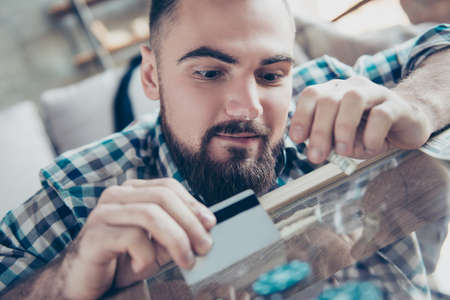 Close up photo of excited cheerful happy drug addict with beard clothed in checkered shirt, he is preparing a sorting line and holding a rolled banknote and credit card