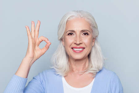 Close up portrait of happy charming cheerful excited with beaming toothy smile mature lady grandmother granny grandma, she is showing okay sign, isolated on gray background