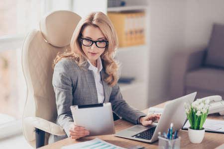 Mujer bonita, encantadora y rubia que usa, navega, escribe, busca, se especializa, trabaja en línea en la computadora y la tableta en el lugar de trabajo, usa internet wi-fi Foto de archivo