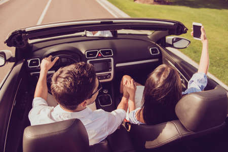 Married brunet family, relax escape, tourism destination, speed ride drive lifestyle. Carefree driver husband, lady wife with camera take shot, make memories of honeymoon road trip, hold arms Stockfoto