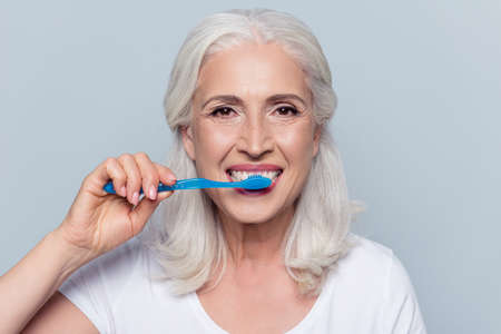 Concept of cleaning teeth is a correct way. Close up photo of happy cheerful mature old lady with good visage brushing her teeth with a blue toothbrush, isolated on gray background