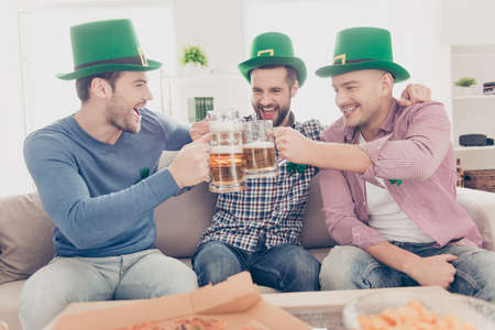 St Patricks day concept. Portrait of laughing, cheerful, positive successful stylish lucky guys with stubble in green hats having glasses with lager in hands, clinking toasting having relax