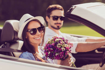 Married family, friendship, trip, relax, chill, escape, speed ride. Well dressed brunet driver in eyewear, femenine girlish lady in cap enjoy her nice pink purple gift present in arm
