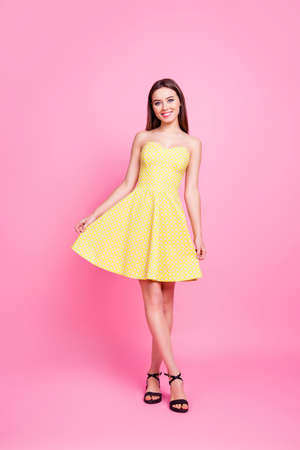 Full length full size portrait of modern, stunning, confident, successful, perfect, charming, nice girl in yellow dress holding bottom of skirt, going standing leg by foot over pink background