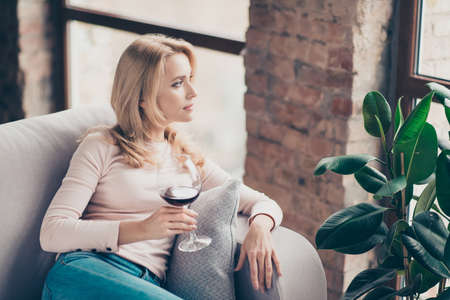 Charming, attractive, pretty, stylish woman, having glass with wine in hand sitting on couch with serious expression looking at window, thinking about something