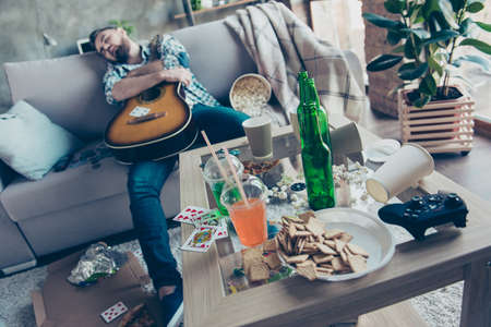 After party morning, bachelorette party. Drunk hipster embracing an acoustic guitar is sleeping on a sofa in messy full of rubbish room